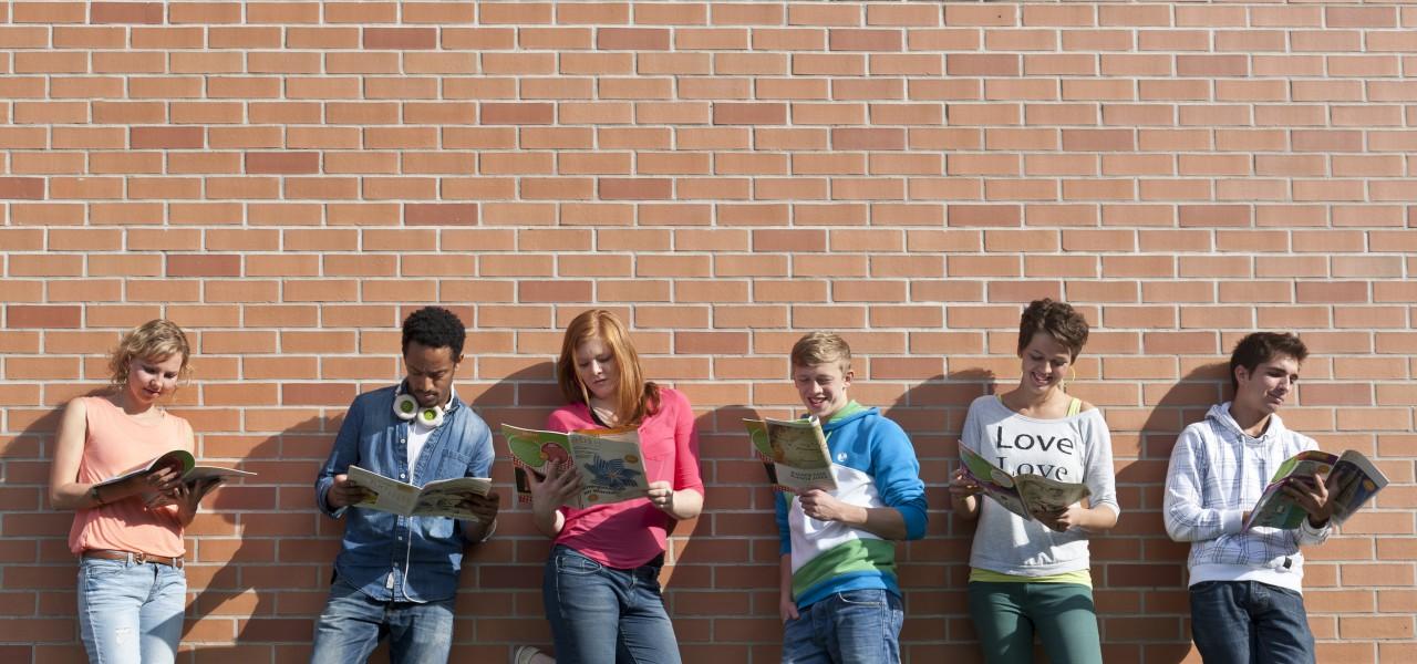Gruppe junger Menschen lehnen an Mauer und lesen