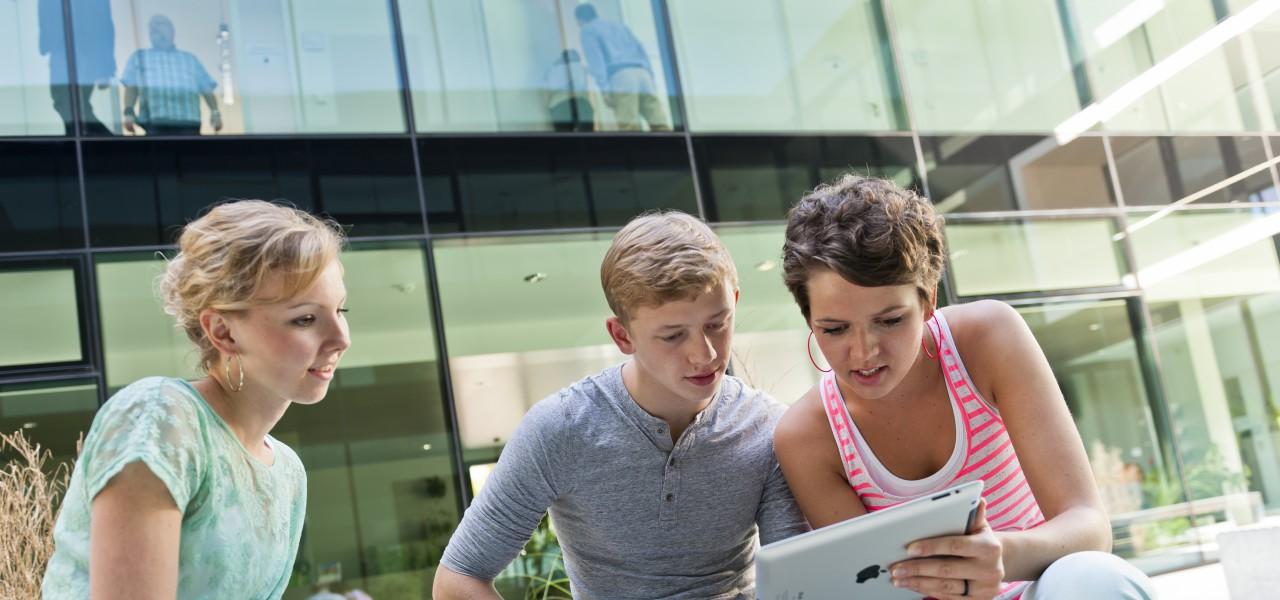 Gruppe junger Menschen befindet sich auf Uni-Campus