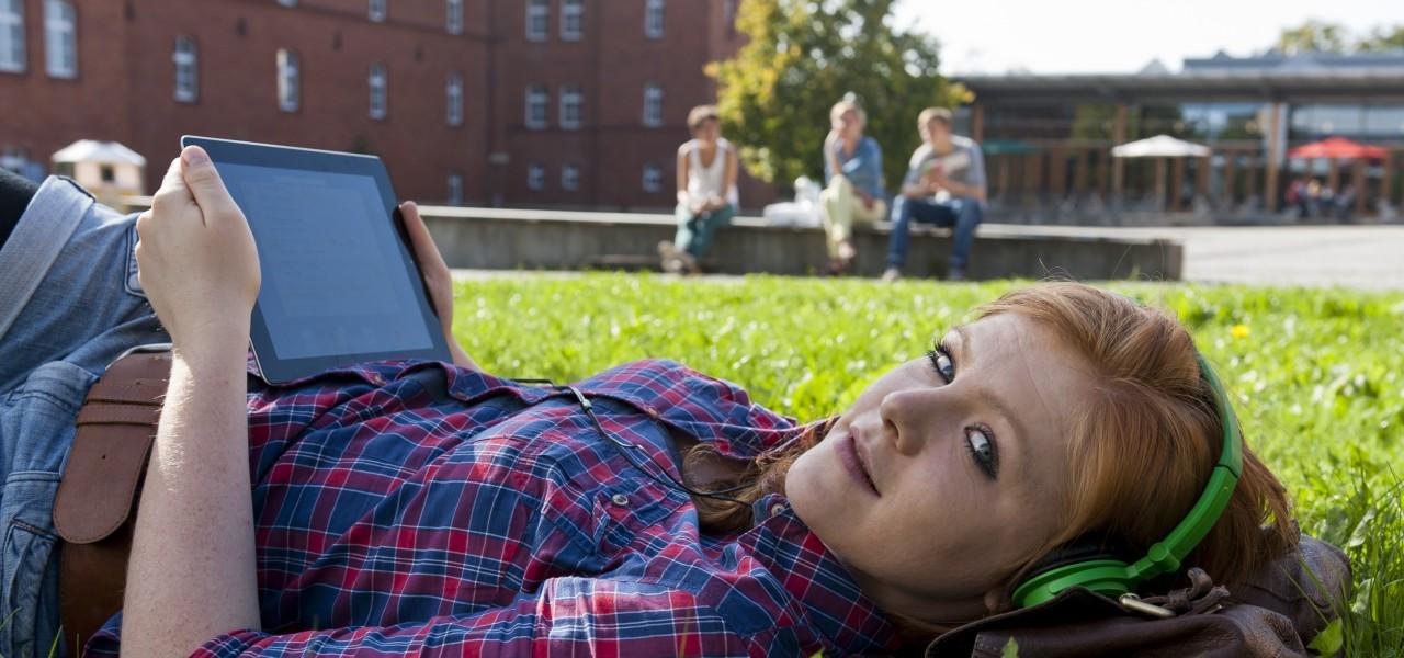 Junge Frau liegt im Grad und hört Musik