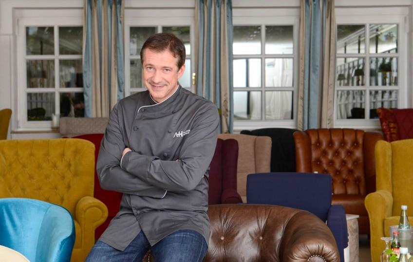 Starkoch Alexander Herrmann sitzt auf einem von vielen bunten Sesseln und lächelt den Betrachter an