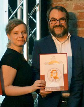 eine Frau und ein Mann blicken in die Kamera. Sie halten eine Auszeichnung in der Hand.
